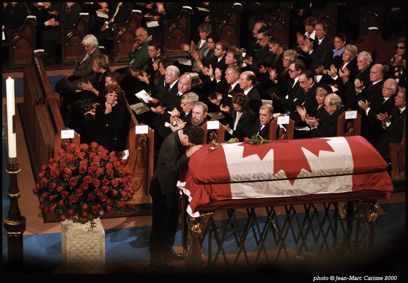The photograph shows former Prime Minister Pierre Elliott Trudeau's family, friends, colleagues, and official guests in attendance to observe his passing. His son, Justin, now the Prime Minister of Canada, rests his head on the casket of his father. Margaret Trudeau, in the front pew with son, Alexandre, is flanked by the beloved prime minister's later life partner, Deborah Coyne, and their daughter, Sarah. The former prime minister's sister, Suzette Rouleau, is on the far side of the same first row. Leonard Cohen on the right. In attendance next to Cuban President Fidel Castro are former Governor-General Romeo Leblanc, His Highness Prince Karim Aga Khan and former U.S. President Jimmy Carter. Other notables present at the ceremony not shown in this photograph include past Canadian Prime Ministers John Turner, Joseph Clark, Brian Mulroney, and Jean Chrétien. Photo: Copyright Jean-Marc Carisse.