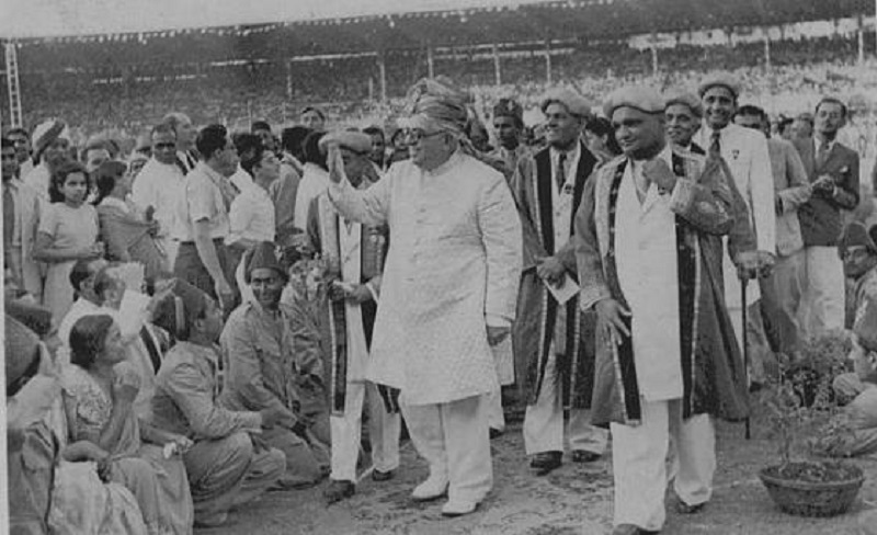 10 March 1946: 48th Imam of the Ismailis, His Highness the Aga Khan III, accompanied by smiling Ismaili leaders, walks by a cheerful and happy group of volunteers at the Diamond Jubilee celebrations held in Mumbai's Brabourne Stadium. The diamonds that he was weighed against were worth 640,000 British pounds and the money was returned by the Imam for the community's social uplifment programs. Photo Credit: Karim Jassani Collection, Ottawa. Mr. Jassani's late father, Itmadi Ebrahim Meherally Jassani, is seen at the right, and walking immediately behind him with a stick is Vazir Kassamali Javeri. In the centre is Varas Daya Vellji, holding an envelope.