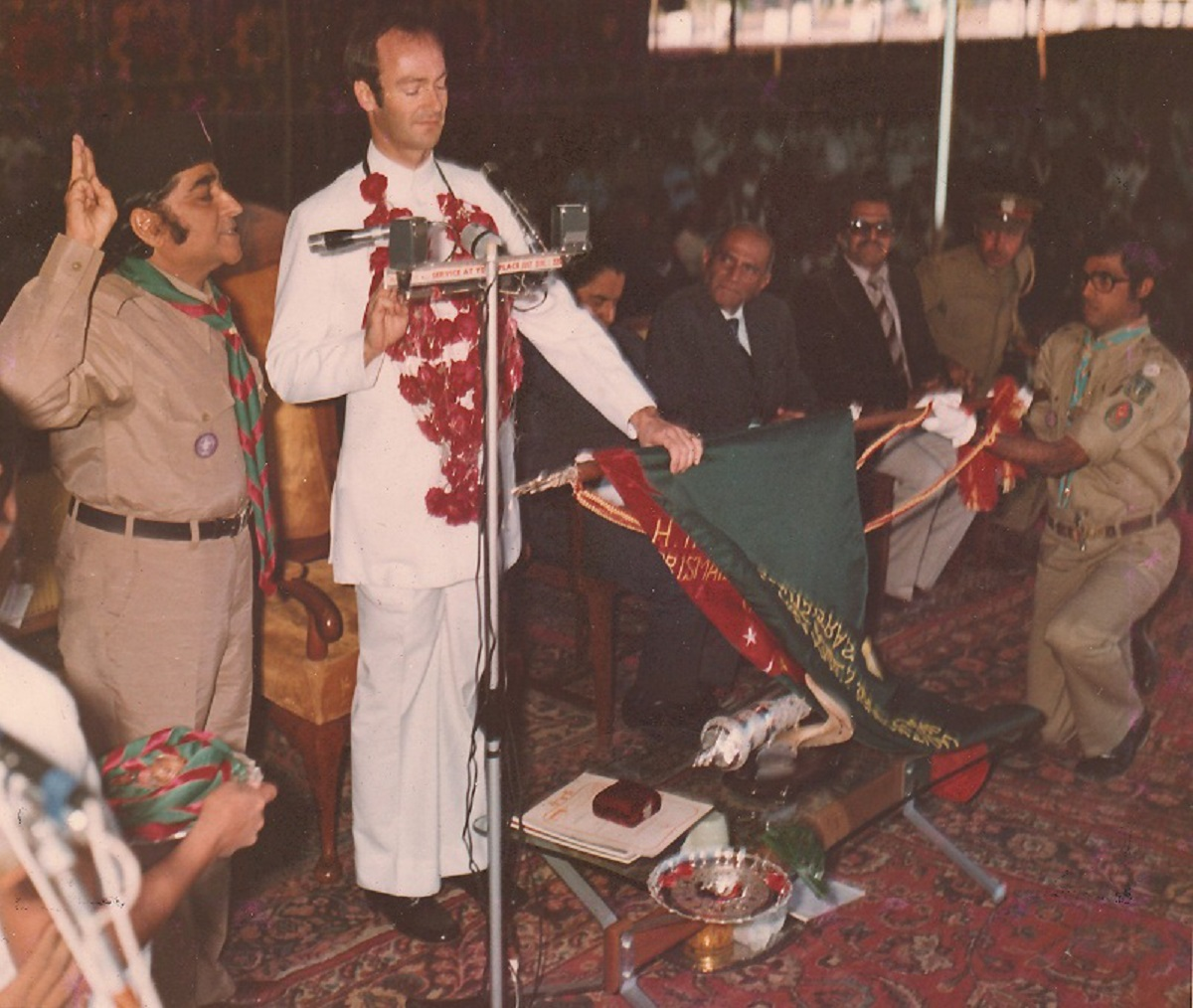 Vazir Sherali Alidina, President of the Scouting Association, left, was in charge of conducting the investiture ceremony, which began with Prince Amyn Mohamed Aga Khan reciting the Scout Promise with his left hand on the flag of the Ismaili Scouts Association and his right hand raised in half salute. The President then wrapped the Scout Scarf on Prince Amyn Mohamed's nape, and pinned the scout badge on his left pocket completing the task with a left-handed scout hand shake with the Prince; the Prince now officially became the second Chief Scout of the Ismailis, following his late father, Prince Aly Khan, who was the first Chief Scout of the Ismailis. The dignified ceremony was short and lasted fifteen minutes. Photo: Khizar Hayat Collection, Toronto, Canada.