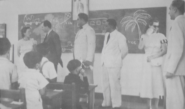 Prince Aly Khan and Rita Hayworth visiting a classroom